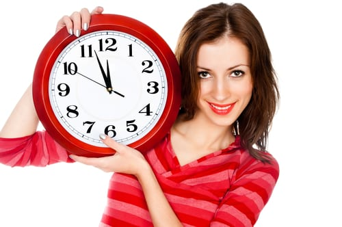 Woman holding a clock signifies Many people with ADHD or Aspergers have trouble managing their time because they have trouble being present in the moment.