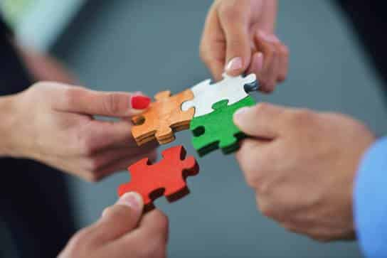 people holding pieces of a puzzle together