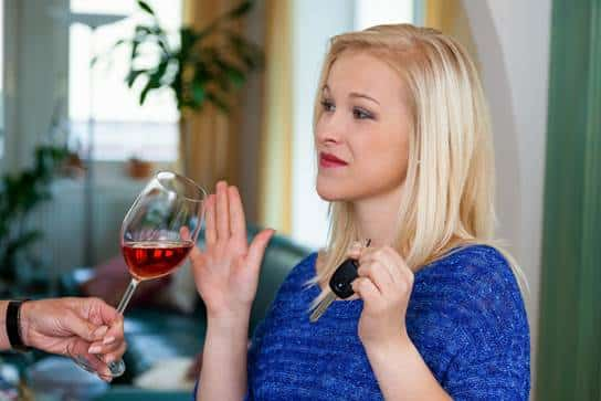 Woman declining a glass of wine