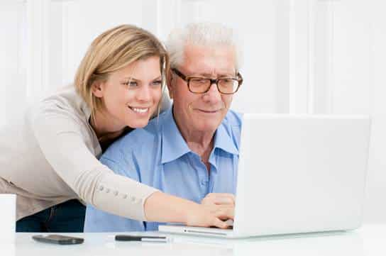 Young woman helping older man with computer