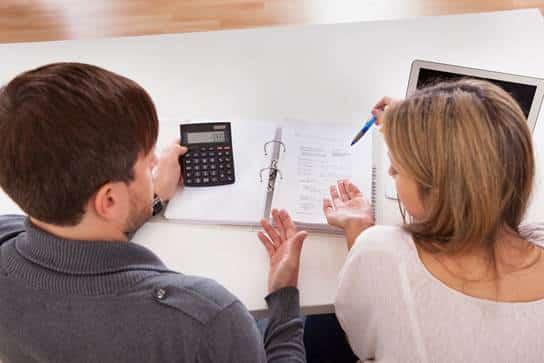 Couple sitting at desk looking at bills