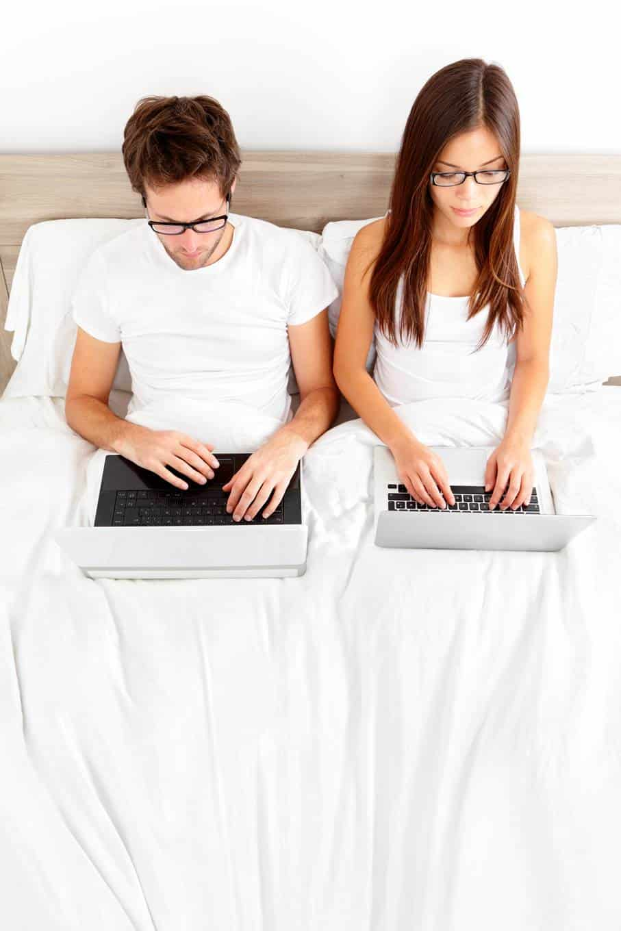 Couple sitting in bed looking at their laptops